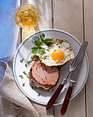 Fried meatloaf with a fried egg on wholemeal bread with butter