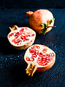 Fresh sliced organic pomegranate on a dark background