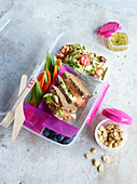 A substantial lunchbox with a pasta salad, vegetable stick and sandwiches