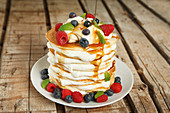 Pancake cake with orange cream, maple syrup and berries
