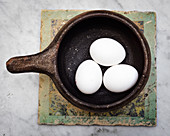 Three white eggs in a ceramic pot