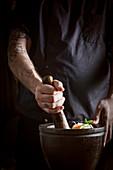 Koch bereitet asiatischen Saloat in Mörser