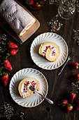 Erdbeer-Biskuitrolle auf weissen Porzellantellern