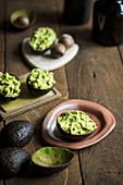 Guacamole in avocado skins on a rustic wooden table