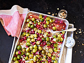 Brussels sprouts and onions on a baking tray with grapes and pomegranate seeds