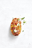 A hasselback potato with caramelized onions and thyme