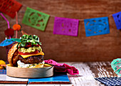 A cheeseburger with lime mayonnaise, guacamole, tomatoes and peppers