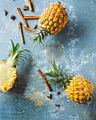 An arrangement of pineapples with cinnamon and star anise