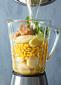 Ingredients for sweetcorn and peanut soup in a blender