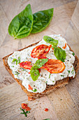 A slice of bread topped with cream cheese, tomatoes and basil