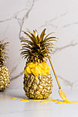 Pineapple ice cream served in a gilded pineapple