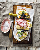 Three great Smørrebrød toppings: Herring and potato, Egg, gherkin and roe, Ham and cheese