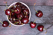 Cherries in a bowl and on a wooden surface (seen from above)