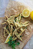 overhead photo of fried Smelt appetizer with lemon and parsley, served on wax paper and wooden cuttingboard