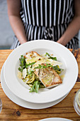 Grilled fish with pasta, rocket, Parmesan and pine nuts