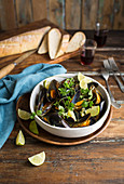 Steamed mussels with coriander leaves and limes