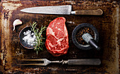 Raw fresh Rib eye Steak, Black Angus, seasoning and fork and knife on dark background