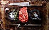 Raw fresh Rib eye Steak, Black Angus, seasoning and fork and knife on dark background