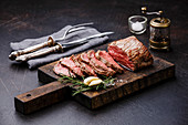 Sliced Tenderloin meat Roast beef on cutting board with knife and fork carving set, saltcellar and pepper mill