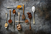 An array of beautifully laid out baking and cooking spices in vintage spoons on a rustic dark surface