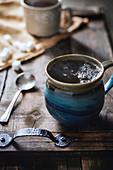 Dampfender heißer Tee in Steinkrug auf rustikalem Holztablett