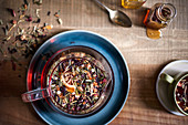 Tray of tea being prepared, loose leaf tea floating in glass teapot with honey jars, spoon and mug