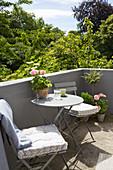 Klappmöbel auf dem sonnigen Balkon mit gemauerter Brüstung