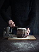 A woman cutting a vegan chocolate Bundt cake