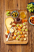 Cheese appetizers with grapes, olives, dried apricots