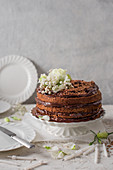Chocolate cake on a white cake stand with flowers