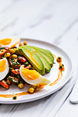 Avocado, chickpea and egg salad with smoked papriake on white wood background with green glass and lime slice