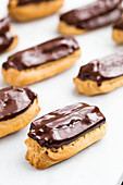 Spelt eclairs made with choux pastry topped with dark chocolate and stuffed with creme patissiere on a wood and marble background