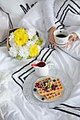 Frühstück im Bett mit Kaffee und Waffeln mit frischen Beeren