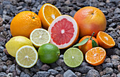 Various citrus fruits displayed on pebbles