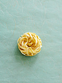 A tagliatelle nest on a textured background