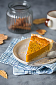 A slice of pumpkin pie on a plate with a spoon