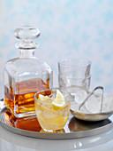 Whisky-Cocktail mit Eis und Zitronenspalten