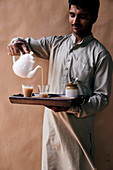 Indischer Kellner gießt Tee in Gläser