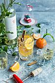 Weincocktail mit Mandarine, Zimtstange und Eiswürfeln