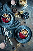 Breakfast bowls with blueberries, cereals, fruit mousse and drinking chocolate