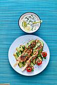 Chicken skewers on cucumber strips with yoghurt sauce