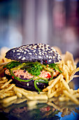 A black burger with crab meat and algae