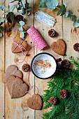Herzförmige Lebkuchenplätzchen, Kaffeebecher und Weihnachtsdekoration auf einem Holztisch