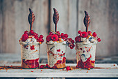 Ice cream in glasses with poppy seeds, gingerbread cream, berries and cinnamon with wooden spoons