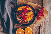 Autumnal porridge with cinnamon, hazelnuts, orange slices, redcurrants and mango