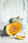 Two Crown Prince pumpkin against a white wooden background