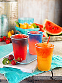 Three different fruity slushies in plastic cups
