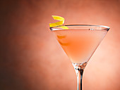 A Cosmopolitan cocktail in front of a coloured background