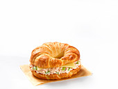 A croissant filled with tuna salad and cheese