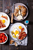 Fried eggs with bacon, tomatoes and poppy seed rolls
